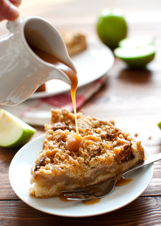 Apple Cookie Crumb Cake - a buttery cookie-like crust, juicy apples, and a delicious streusel topping. A drizzle of caramel sauce takes it over the top. Perfect! | thetoughcookie.com