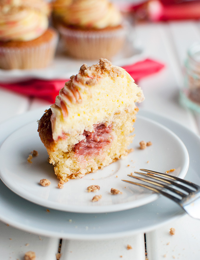 Rhubarb and Custard Cupcakes - These delicious cupcakes are filled with rhubarb puree and topped with a swirl of custard buttercream, rhubarb syrup, and crunchy crumb topping. Yum! | thetoughcookie.com